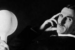 Tesla holding a phosphor-coated wireless light bulb