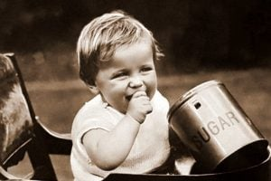 Toddler in highchair with sugar jar