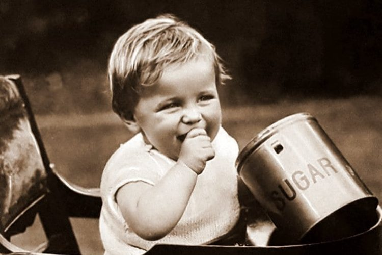 Toddler in highchair with sugar jar