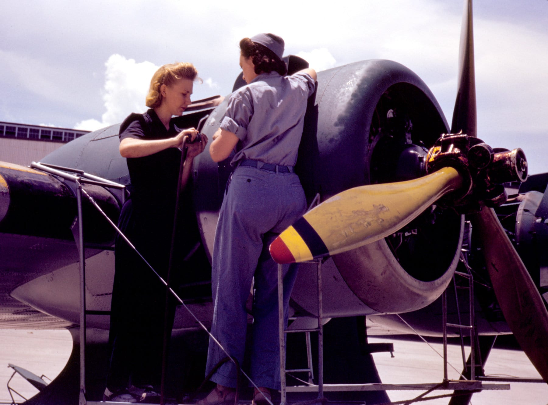 Two women repairing a WWII propeller plane engine