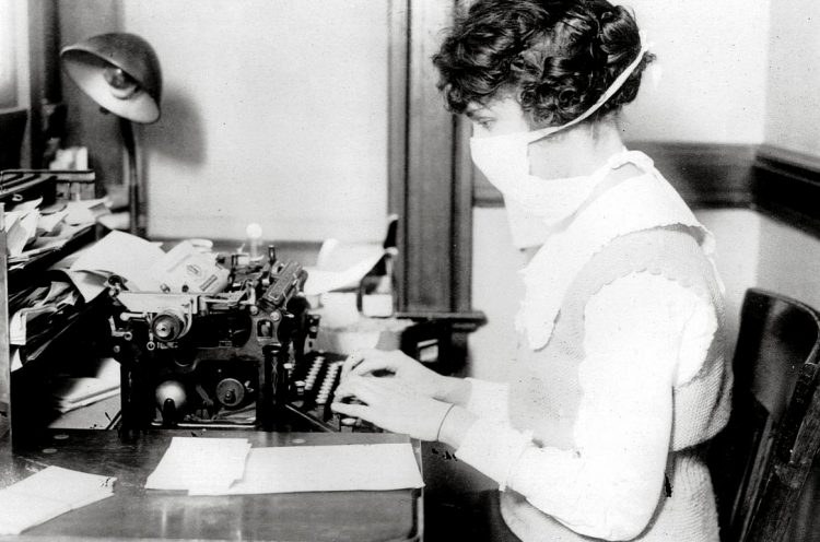 Typist wearing mask for influenza, New York City, October 1918