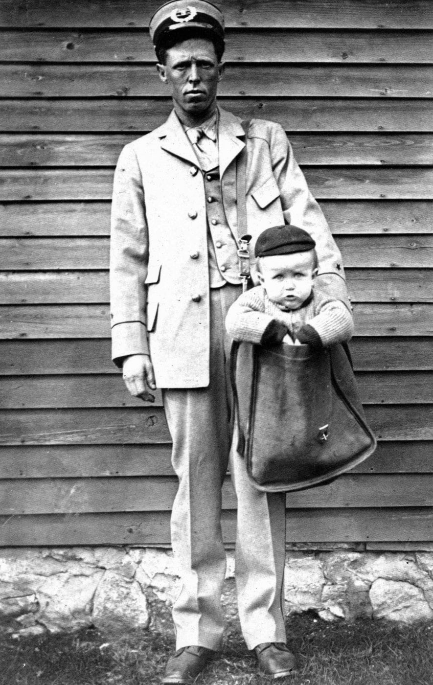 Uniformed Letter Carrier with Child in Mailbag 1913