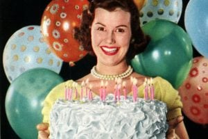 Vintage 1950s woman with a cake and cake recipes