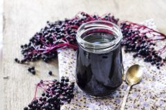 Homemade black elderberry syrup in glass jar