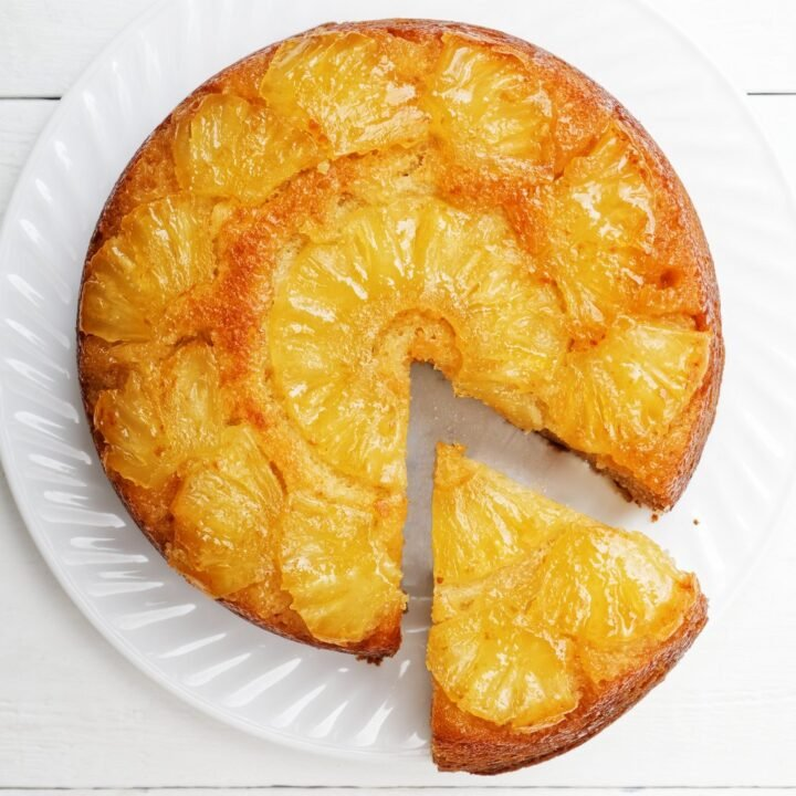 Pineapple Upside Down Cake and cup of coffee on white wooden tab