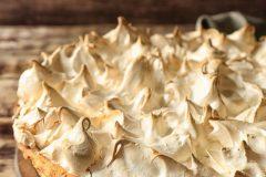 Board with tasty lemon meringue pie on wooden table, closeup