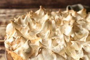Board with tasty lemon meringue pie on wooden table, closeup