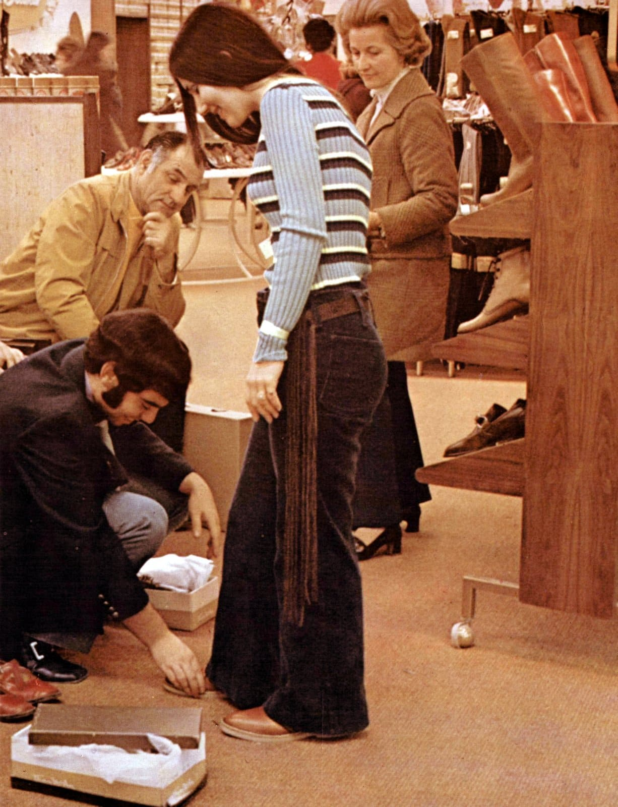 Vintage shoe shopping for a teen girl wearing bell-bottoms (1970)