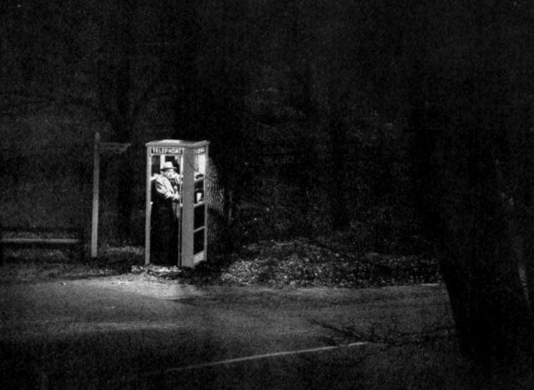 Vintage street payphone at night in 1956