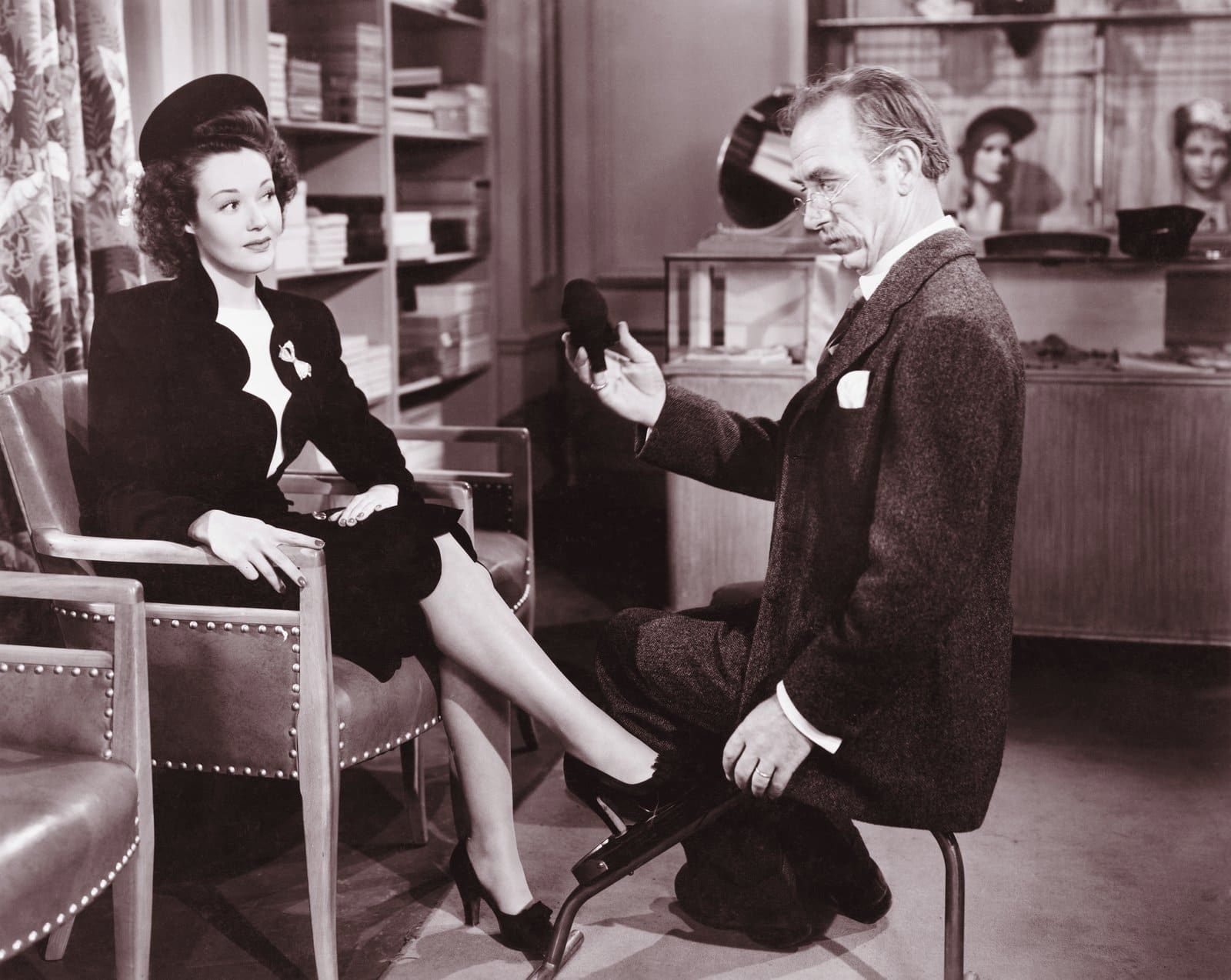 Woman trying on shoes with help of a salesperson (c1940s)