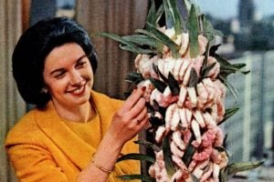 Woman with a vintage shrimp appetizer tree in 1965