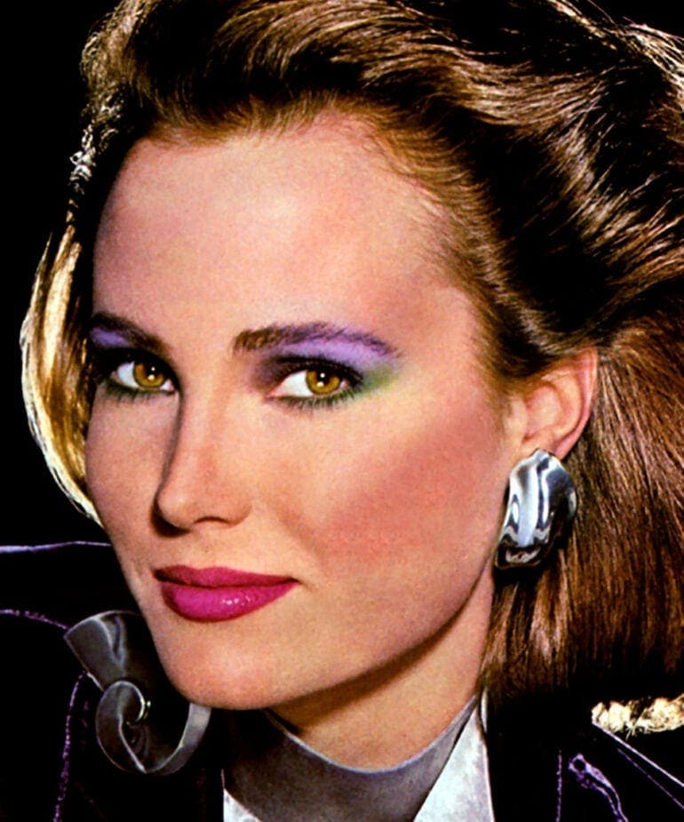 Woman with multicolored eyeshadow and big 80s earrings
