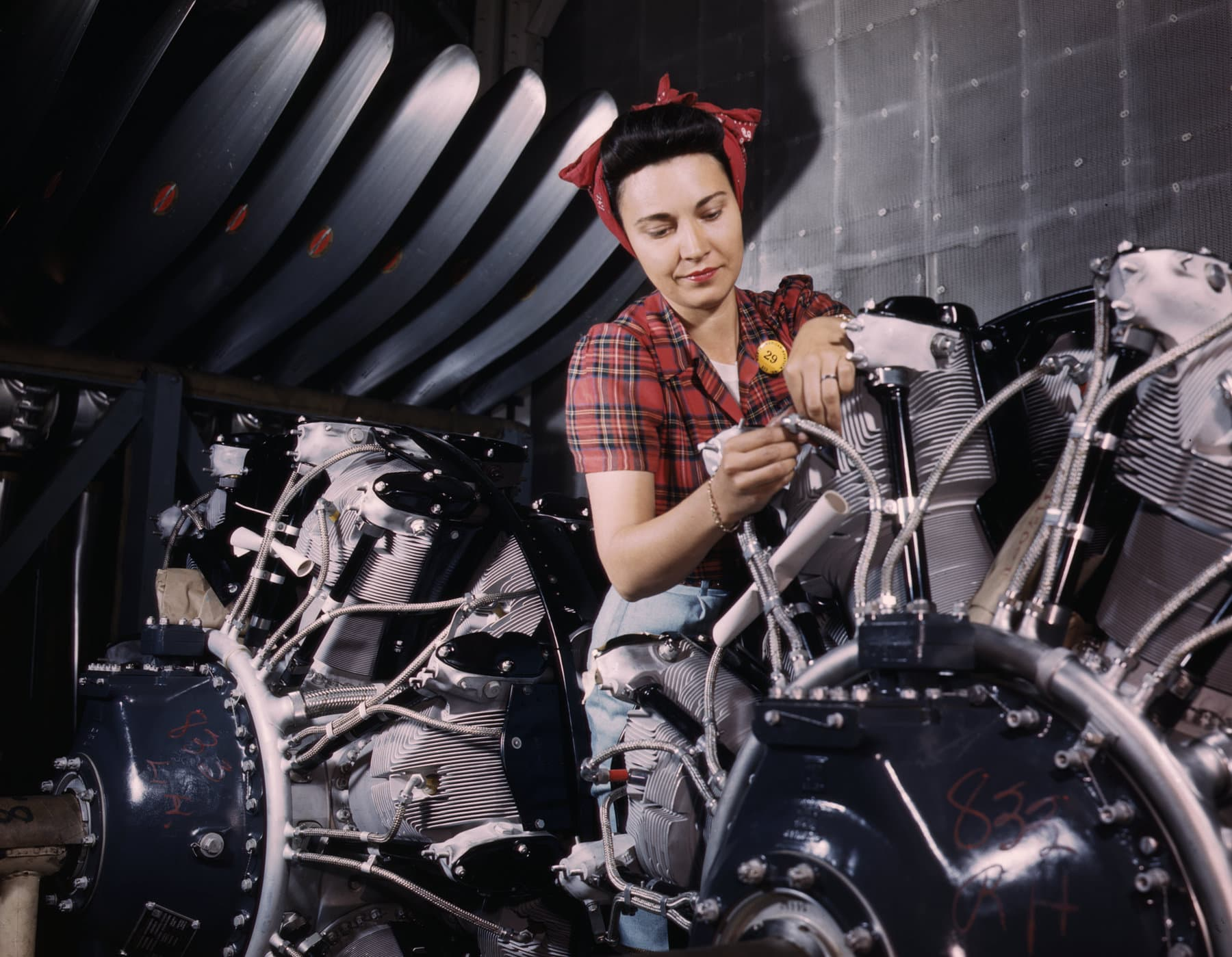 Woman working on an airplane motor for a WWII fighter plane