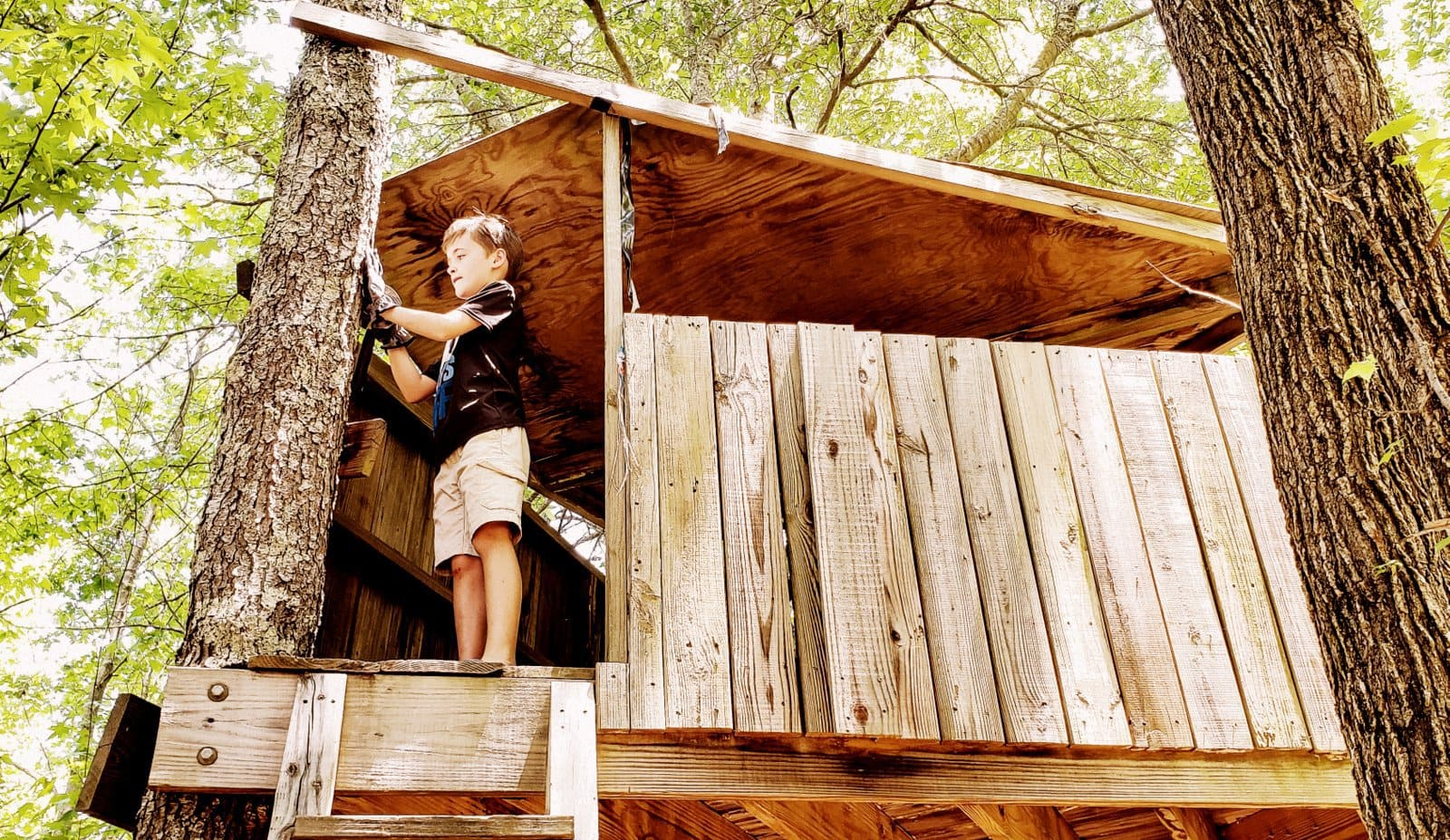 Young boy working on an old-fashioned wooden treehouse fort