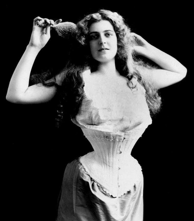 c1899 Woman wearing corset, brushing her hair