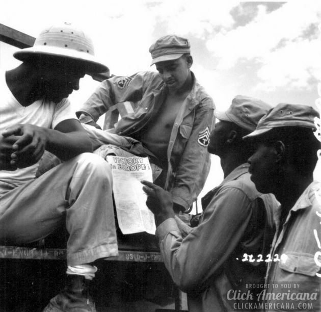 troops in Burma stop work briefly to read President Truman's Proclamation of Victory in Europe